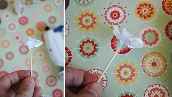 Adding hot glue to secure flower to toothpick