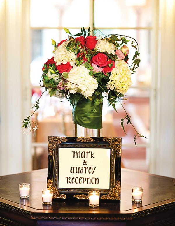 Wedding decorated in purple, pink and gold. Reception sign with flowers and candles