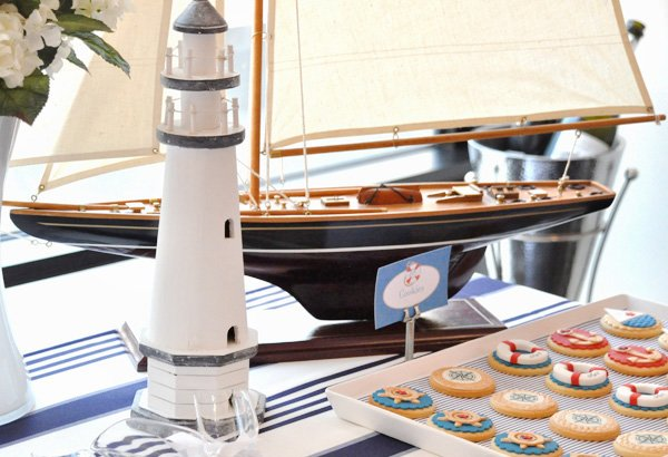 nautical christening party sailboat and lighthouse decoration on the dessert table