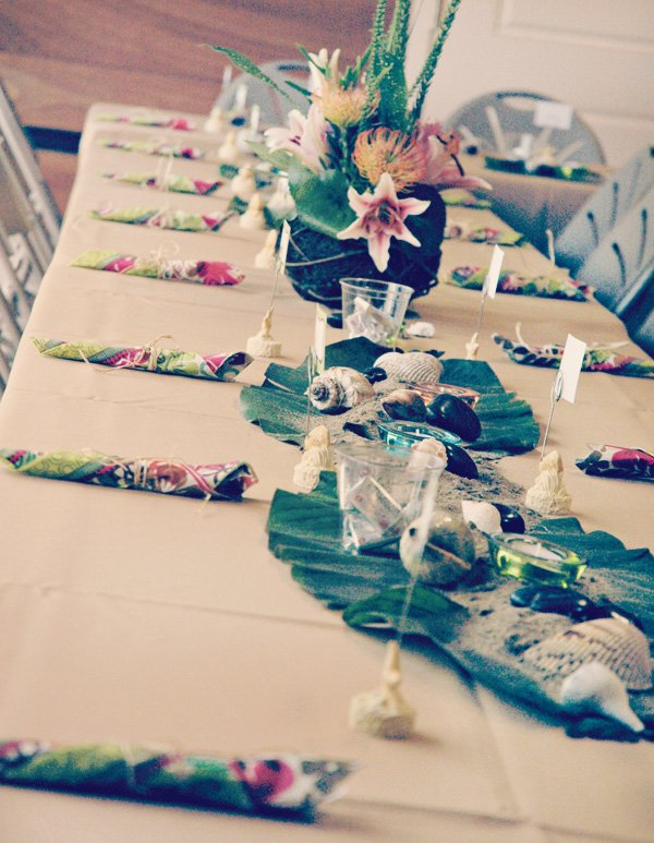 hawaiian luau dinner party table decorations with sand and beachy theme