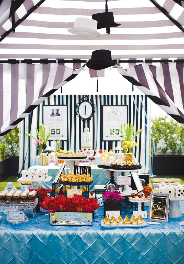 monopoly birthday party desserts in a black and white striped tent