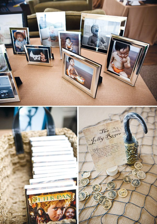 neverland inspired first birthday party picture frames and peter pan books. Table centerpieces with netting and gold coins for captin hook