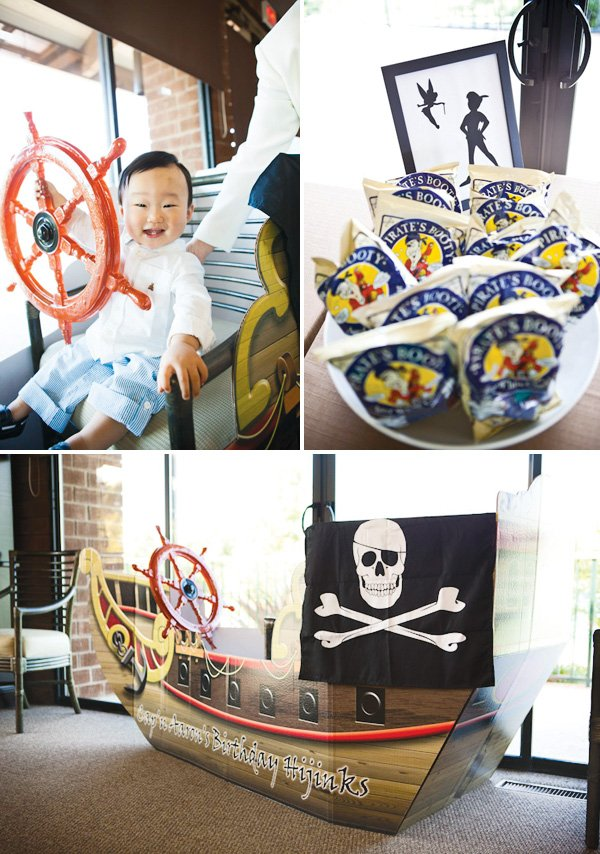 neverland inspired first birthday party pirate ship booty chips and peter pan and tinker bell. The birthday boy is riding the pirate ship.
