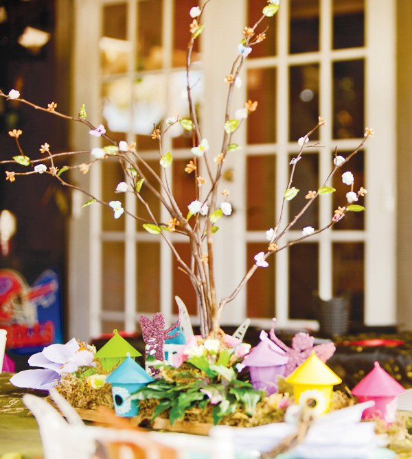 tinkerbell party centerpieces that look like trees with tiny flowers and birdhouses at the base