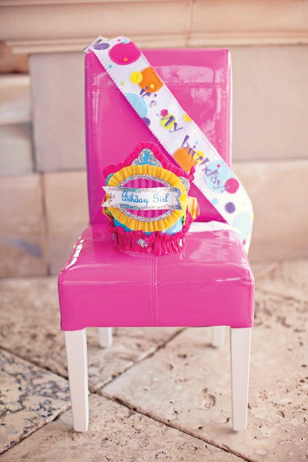 hot pink chair with pink yellow teal birthday crown