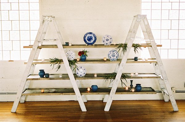 dutch plates displayed on white ladders is such a creative room decoration display for a party