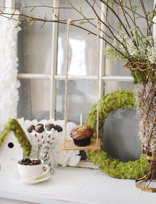 Dessert table centerpiece idea with a mini tree swing displaying a cupcake