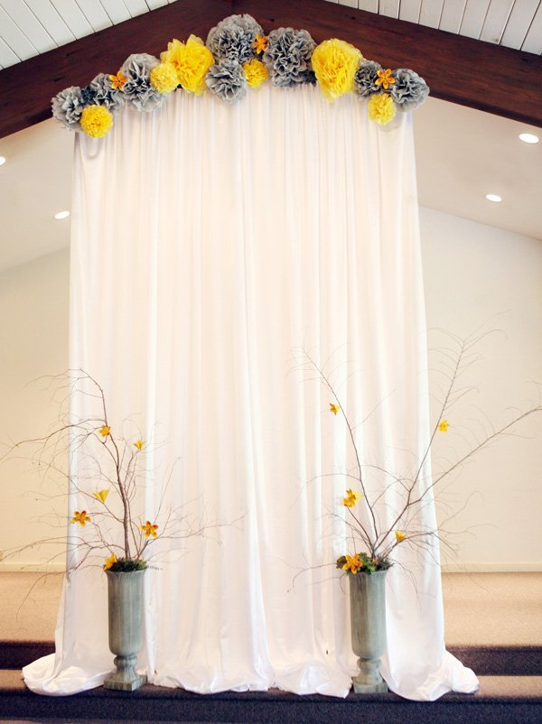 modern gray and yellow wedding stage with tissue poms