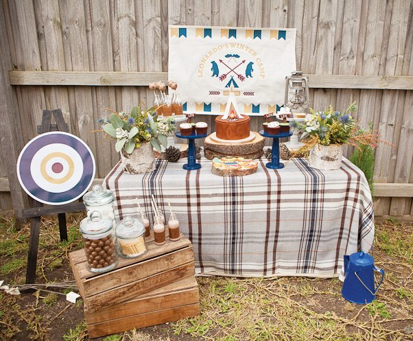 Camping party dessert table with tree stump cake stand