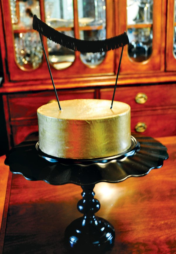 gold cake with a black fringe bunting cake topper