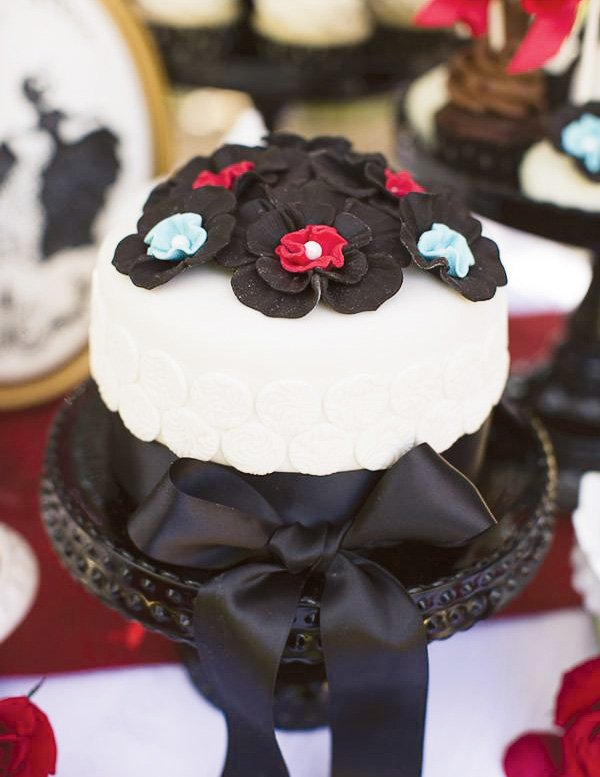 "Mary Poppins ""Jolly Holiday"" inspired cake with black, red, and light blue flowers"