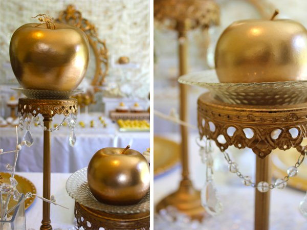 gold candlesticks topped with gold apples