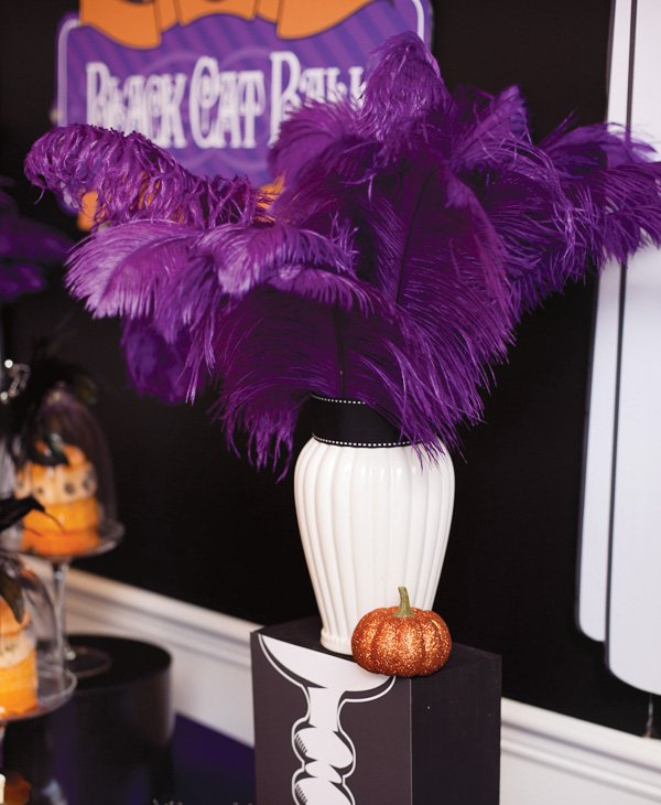 White vase centerpiece with black ribbon and purple feathers