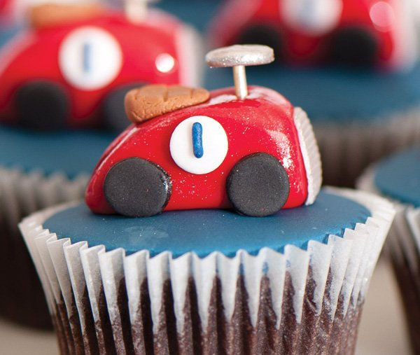 vintage car cupcake topper on a blue frosted cupcake