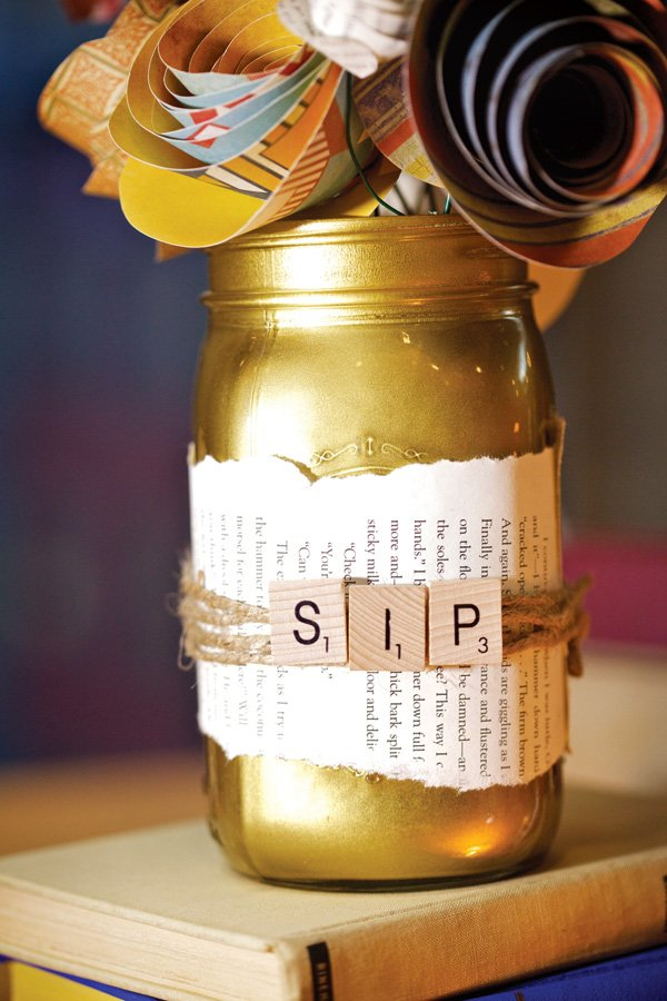 gold mason jar with scrabble tiles and book pages
