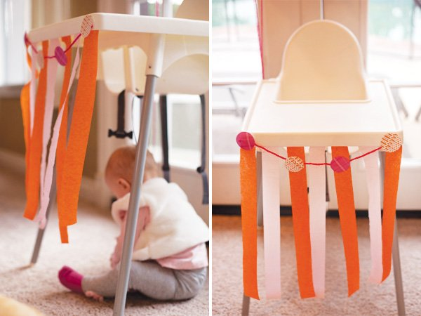 first birthday high chair decorated with crepe paper and party circles