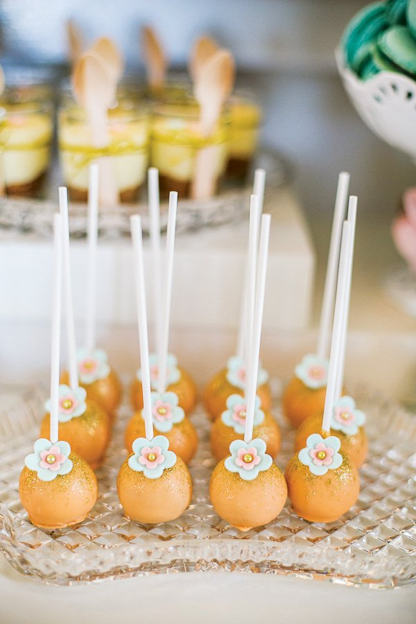 orange glitter dusted and flower embellished cake pops