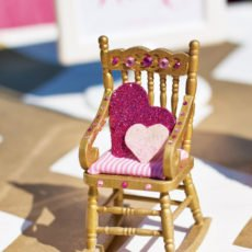 gold rocking chair with pink heart pillows