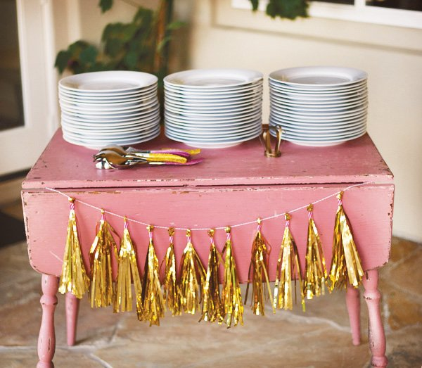 gold tassel plates on a vintage pink table