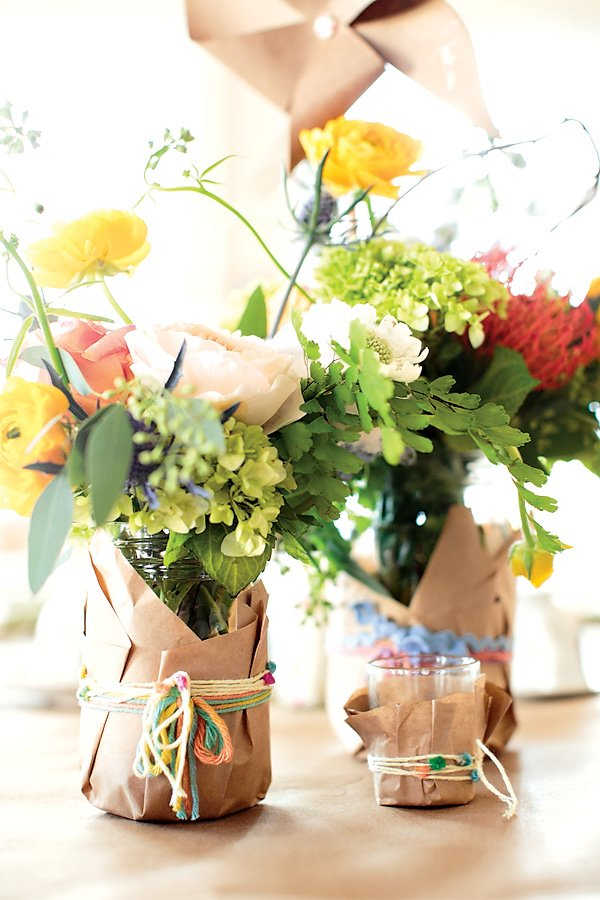 Mason jar centerpieces wrapped in craft paper and yarn