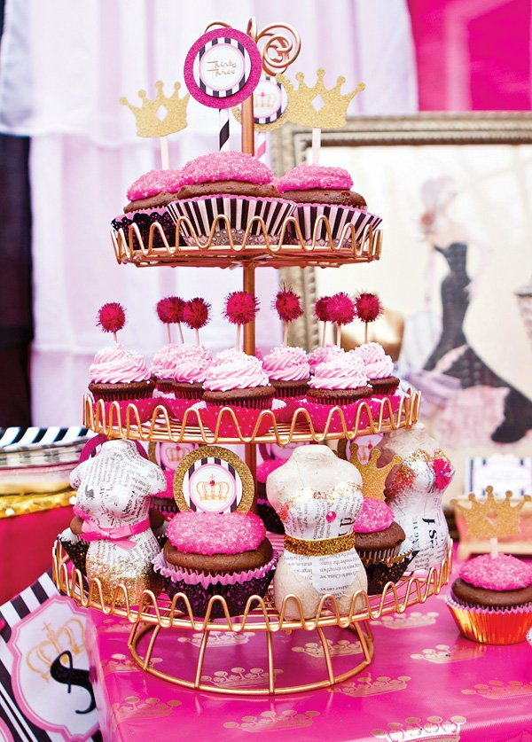 cupcake tower with pink pom-poms, gold glitter crown toppers, and paper mache figure forms