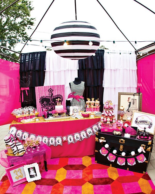 a black and white striped lantern, bright rug and dessert table for a glam black, white and pink birthday party