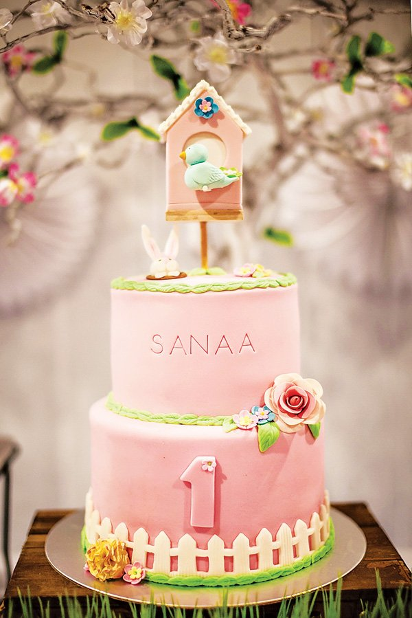 a beautiful pink and green first birthday cake with a picket fence, flowers, garden animals, stamped name and a birdhouse
