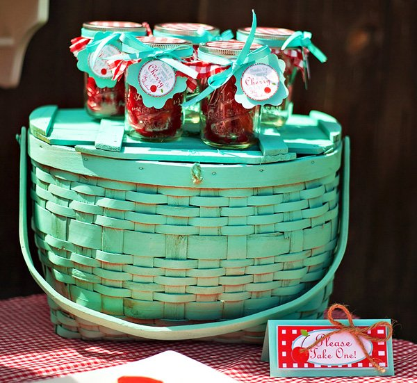 a teal painted basket with cherry pie mason jars filled with red licorice for party favors