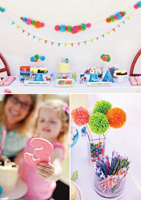 A colorful pony party dessert table with pom-pom garlands, frosted cookies, and pom flowers