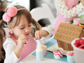 girl decorating a gingerbread house