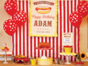 hot dog themed dessert table with hot dog garland, sunflowers, red and white striped fabric and a hot dog cake