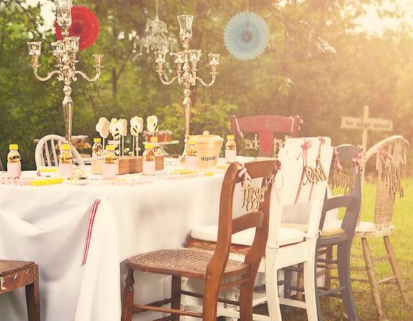 magical winnie the pooh party table with mismatched chair and hanging painted lanterns