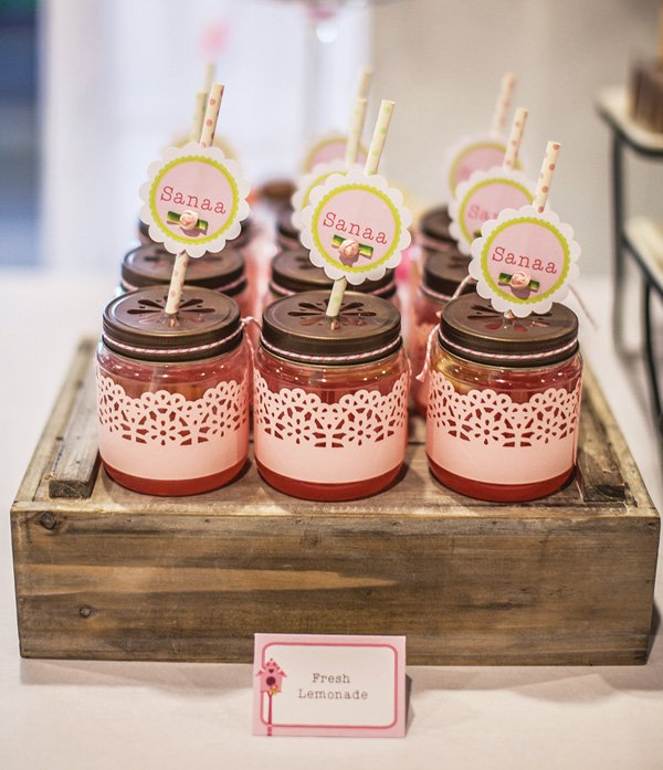 pink lemonade in mason jars with paper straws and light pink lace paper wrap or a girl's birthday party drinks