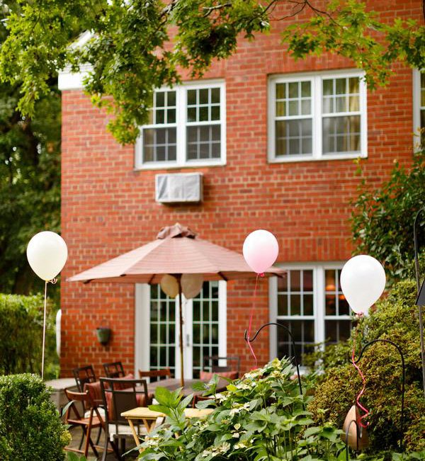 backyard birthday brunch venue with pink and white balloons