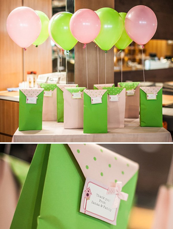 pink and green polka dotted party favor bags with balloons tied on top
