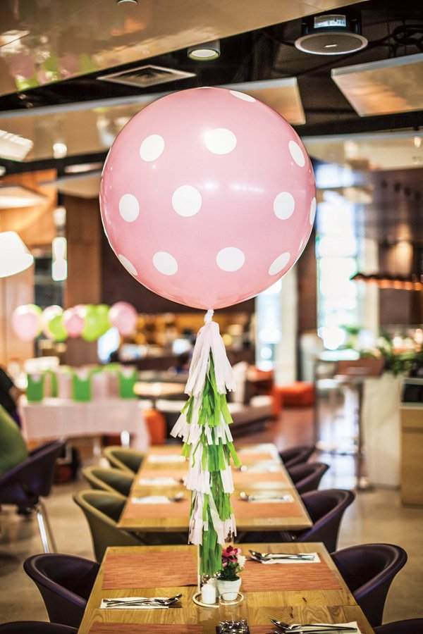 big pink polka dot balloon and green and white tassel garland centerpiece