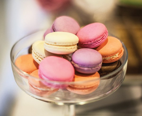 a dish of pink purple. orange and yellow french macarons for a birthday party