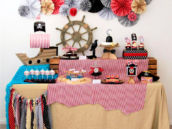 pirate birthday party dessert table with red and white fabric, a ship, and wheel