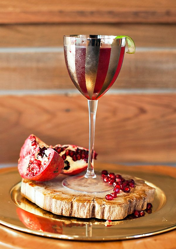 a pomegranate cocktail on a wooden coaster in a goblet