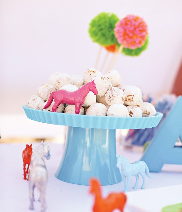 blue cake stand with toy horses and powdered doughnuts