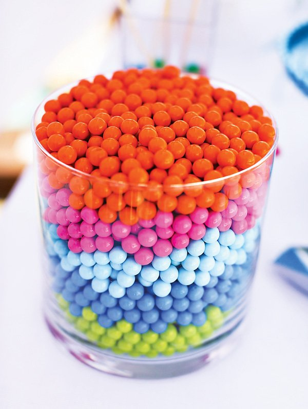 a vase filled with a rainbow of orange, pink green and blue sixlets