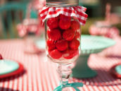a mason jar stemmed glass with red gingham fabric, teal ribbon and filled with red gumballs