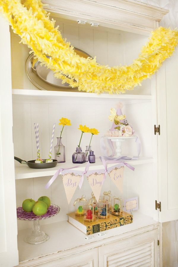 tangled birthday party fringed hair garland over a bookcase