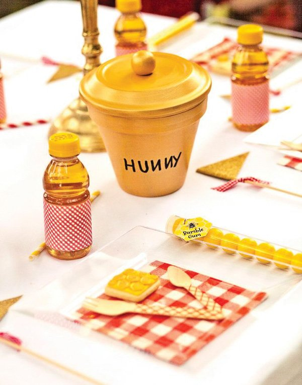 winnie the pooh party table setting for kids with red gingham, wooden utensils and hunny pot