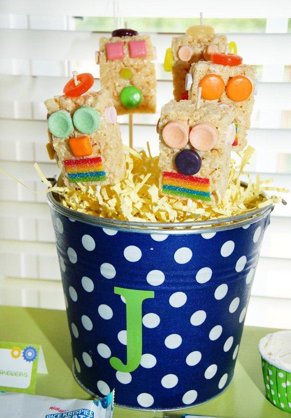 a bucket of rice krispie robots on sticks