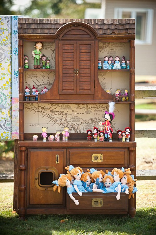 stuffed plush dolls as peter pan party favors displayed in a cupboard