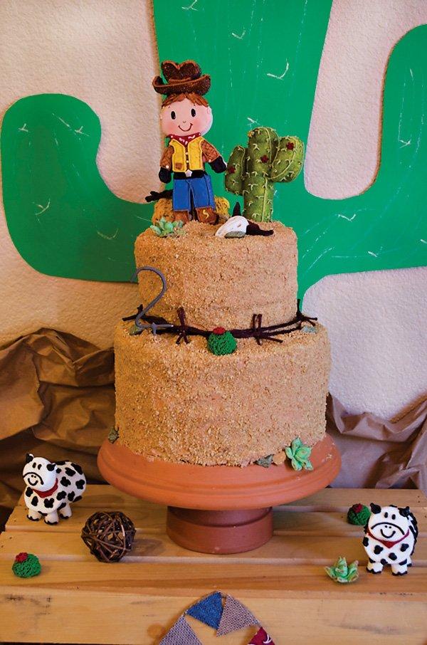 western cowboy cake topper on a sandy desert birthday cake