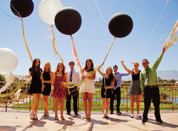 giant black and white balloons with pink feather boas and gold tinsel and fringe for a parisian party