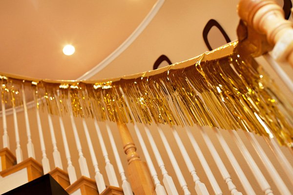 a gold tinsel garland on the stair's banister for a fiesta