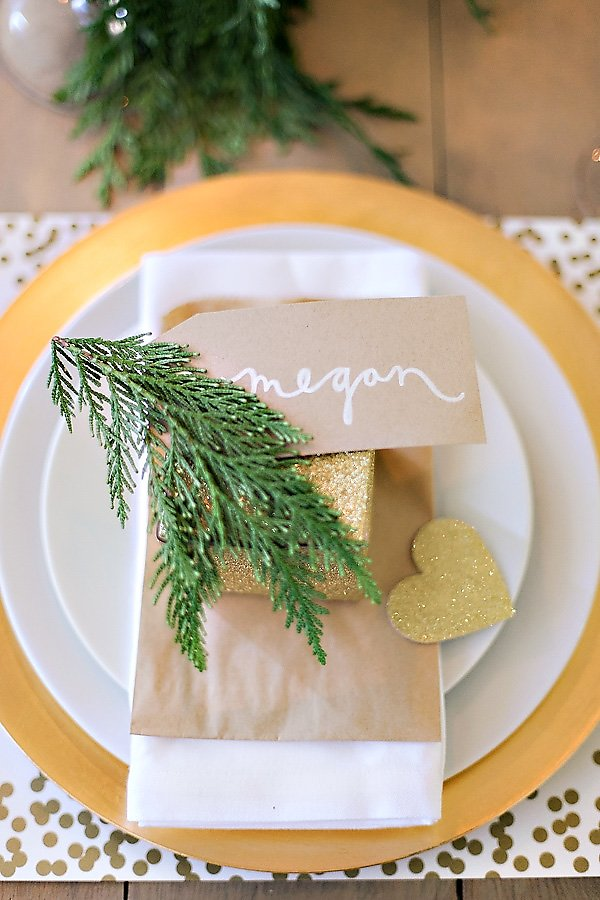 pretty white and gold place setting with christmas tree branches for a holiday party